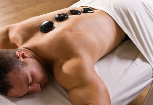 Man receiving hot stone therapy massage